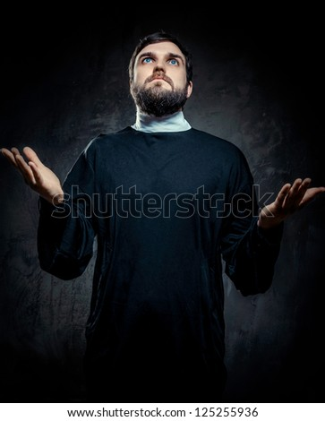 Portrait of priest against dark background - stock photo