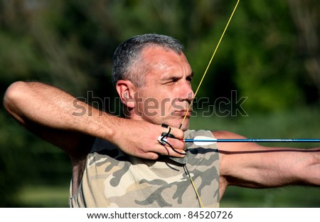 Portrait of professional bowman aiming with bow and arrow - stock photo