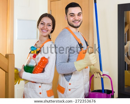 Portrait of professional cleaners with equipment at the doors of client house
