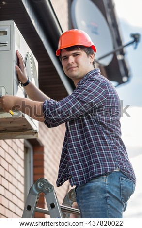Portrait of professional electrician repairing air conditioner on outer wall of building - stock photo