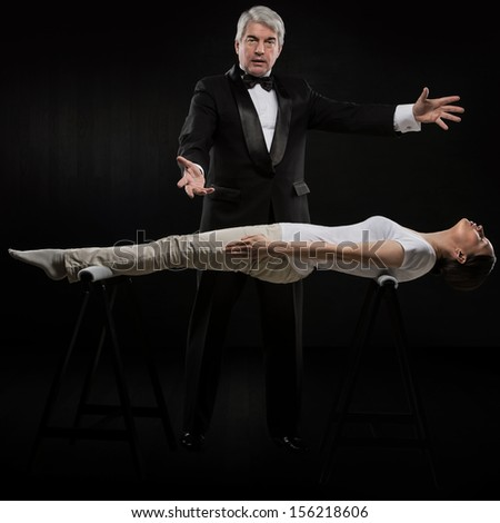 Portrait of professional hypnotist on black background working with young woman - stock photo