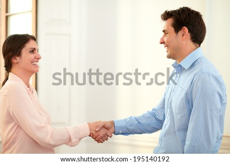 Portrait of professional man and woman giving hands greeting each other while smiling and standing on office background