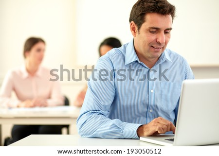 Portrait of professional man working and looking on his laptop while in background a female is sitting with her colleague on workplace
