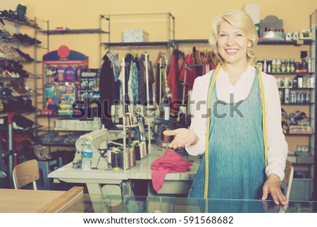 Portrait of professional mature female tailor standing in sewing atelier