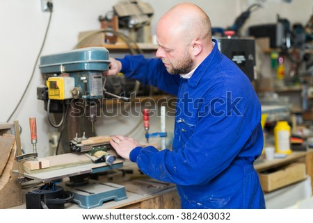 Portrait of professional woodworker working on a machine at guitar workshop