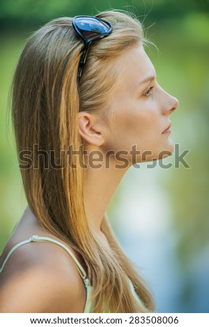 Portrait of profile young beautiful woman against summer garden. - stock photo