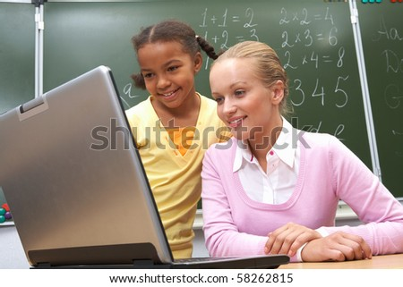 Portrait of pupil and teacher looking at the laptop in classroom