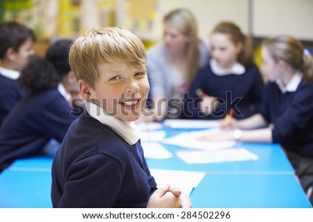 Portrait Of Pupil In Classroom With Teacher - stock photo