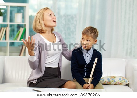 Portrait of pupil with the flute looking at his tutor speaking about music with admiration - stock photo