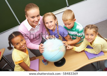 Portrait of pupils and teacher looking at camera with globe on table during geography lesson