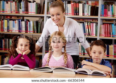 Portrait of pupils and teacher looking at camera with smiles in library - stock photo