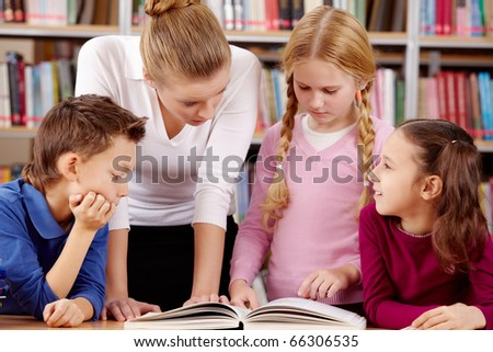 Portrait of pupils and teacher reading and discussing interesting book in library - stock photo