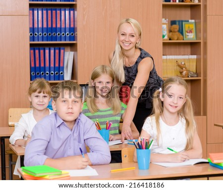 Portrait of pupils and their teacher in a classroom - stock photo