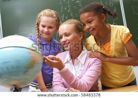 Portrait of pupils looking at globe being pointed at by lecturer during lesson - stock photo