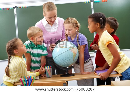 Portrait of pupils looking at globe while listening to teacher during geography lesson - stock photo