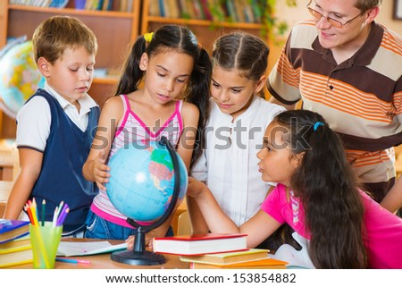 Portrait of pupils looking at globe with their teacher during geography lesson  - stock photo