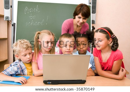 Portrait of pupils looking at the laptop display with teacher near by - stock photo