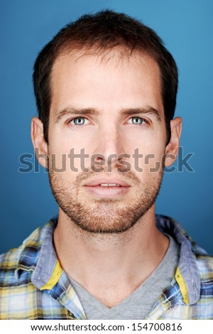 portrait of real man face looking at camera on blue background - stock photo