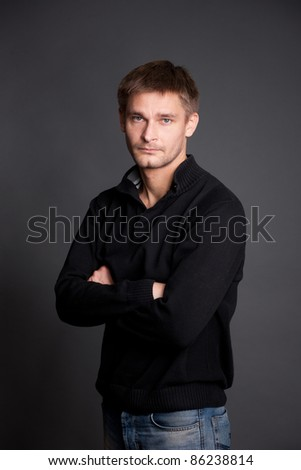Portrait of real man posing for camera on grey background