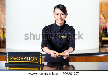 Portrait of receptionist passing keycard in hotel - stock photo