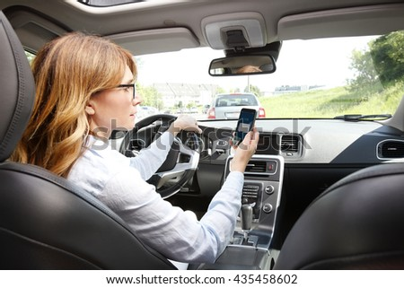 Portrait of reckless driver using her mobile phone while driving car.