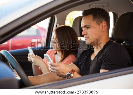 Portrait of reckless young adults texting on their smartphones and driving, ignoring the road - stock photo