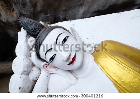 Portrait of Reclining Buddha in Kaw-goon ancient cave at Kaw-goon Village, Hpa-an, Kayin State, Myanmar. - stock photo