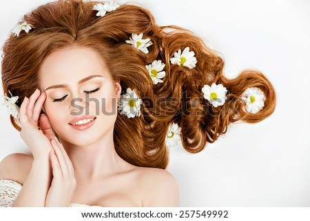 Portrait of red-haired beautiful and gentle girl with daisies in their hair lying on the floor with closed eyes , on a white background in Studio - stock photo
