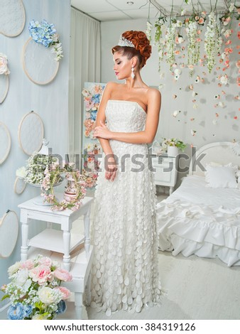 portrait of red-haired bride in interior. wedding dress, make-up.