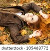 Portrait of red-haired girl in the autumn park. Outdoor shot. - stock photo