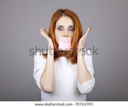 Portrait of red-haired girl with colorful funny stickers on mouth. Studio shot.