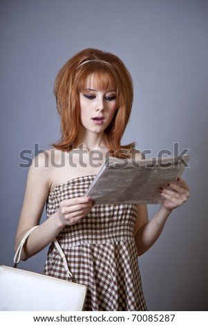 Portrait of red-haired girl with newspaper. 60s style. - stock photo