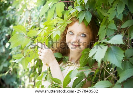 Portrait of redhead girl with blue eyes on nature. Face of young woman with freckles closeup - stock photo