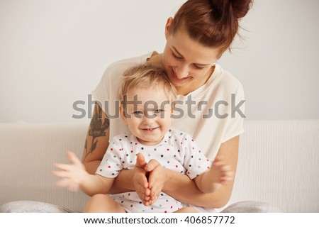 Portrait of redhead mother having fun with her blond son indoor with toddler looking at camera with joyful expression. Happy mother enjoying upbringing her adorable child. Pastel colors, cozy scene - stock photo
