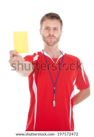 Portrait of referee blowing whistle while showing yellow card over white background