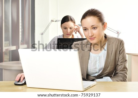 Portrait of relaxed and happy business woman in an office environment working with laptop