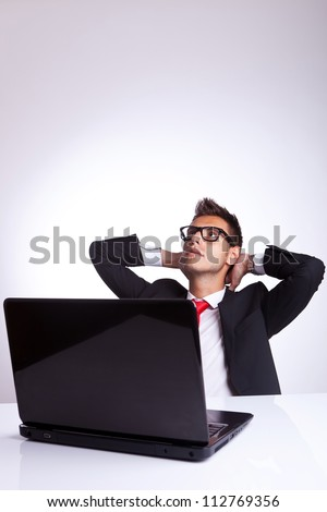 Portrait of relaxed business man in front of laptop
