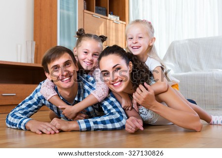 Portrait of relaxed family of four posing in domestic interior