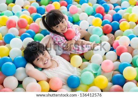 Portrait of relaxed little sisters lying among colorful balls - stock photo