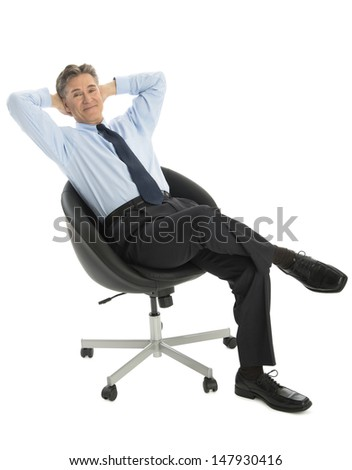 Portrait of relaxed mature businessman with hands behind head sitting on office chair against white background