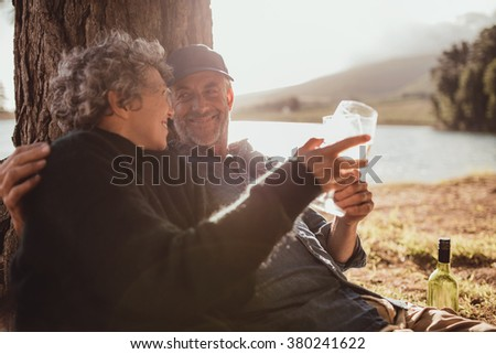 Portrait of relaxed mature couple sitting at a tree and toasting wine. Senior man and woman enjoying drinking wine at campsite on summer day. - stock photo