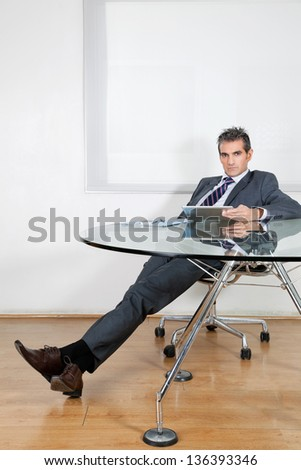 Portrait of relaxed mid adult businessman using digital tablet at desk in office - stock photo