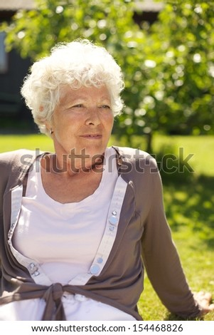 Portrait of relaxed old lady sitting on grass looking away - Outdoors - stock photo
