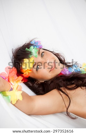 Portrait of relaxed pretty young woman with accessories in Hawaii style lying in white hammock - stock photo