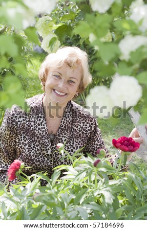 Portrait of relaxed senior woman in a blossoming garden