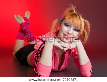 Portrait of relaxed young lady smiling while lying o floor in studio - stock photo