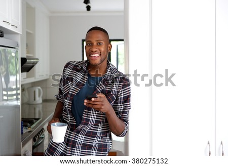 Portrait of relaxed young man standing in kitchen holding cup of coffee and mobile phone - stock photo