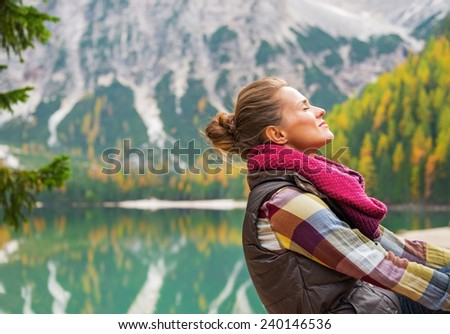 Portrait of relaxed young woman on lake braies in south tyrol, italy - stock photo