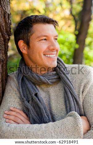Portrait of relaxing man on tree enjoying golden autumn fall season - stock photo