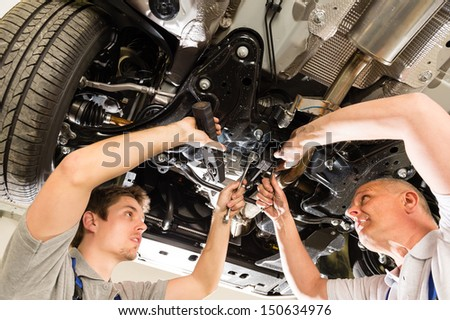 Portrait of repairmen under a car working together - stock photo